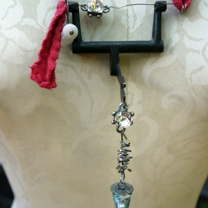Recycled sewing machine part with hanging charm necklace